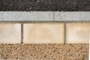 Threshold boundary with resin natural stone and tarmac